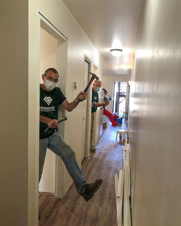 Volunteers show off their tools at a HeroWork renovation site. The charity, which renovates other charities, organizes its renovations around community events that often include meals and music.
