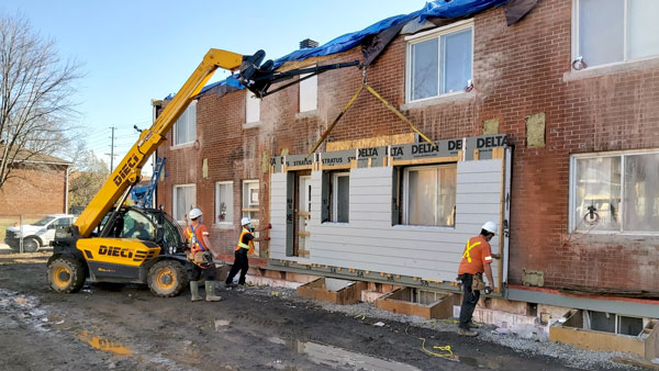 The answer to the challenge of an aging and energy inefficient housing stock is the erection of prefabricated energy-efficient panels, suggested Mark Carver, who heads Natural Resources Canada's Prefabricated Exterior Energy Retrofit project. Pictured are walls being put up at an Ottawa Community Housing project.