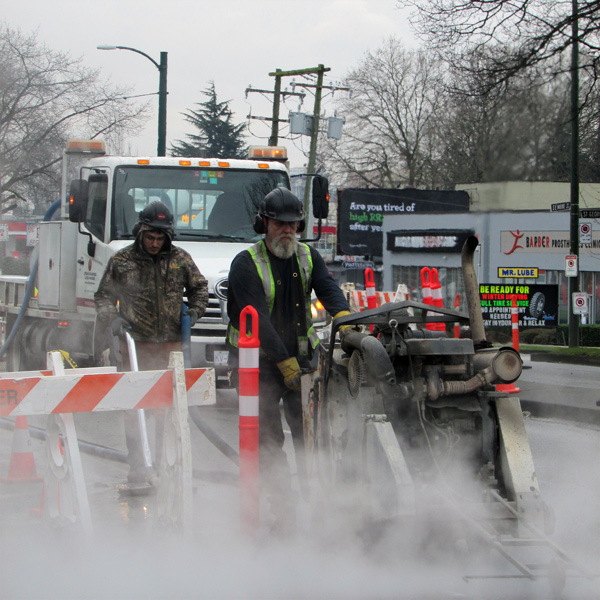 An Urban Sawing and Scanning crew use a pavement saw to begin the trench work that will provide city crews access to water and sewer lines replaced over a five kilometre stretch from Victoria Drive to Oak Street in Vancouver.